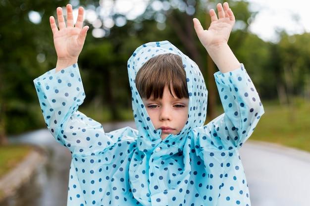 Dzieciak ubrany w niebieski płaszcz przeciwdeszczowy w kropki
