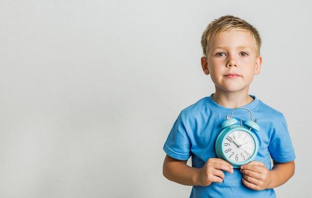 Dzieciak w przypadkowych ubraniach trzyma zegar