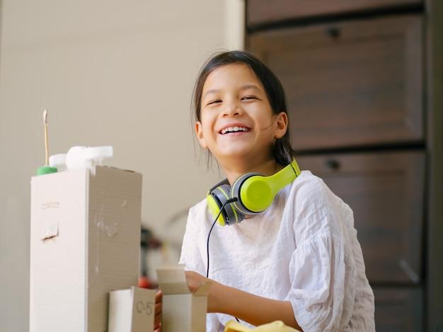 Dzieciak w szkole z rękodziełem z recyklingu i upcyklingu. recykling pomaga ocalić planetę, uczy dzieci wytwarzać mniej odpadów. działania twórcze dla dzieci.