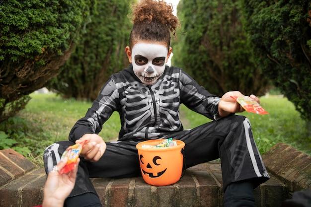 Dzieciak w uroczym, ale przerażającym kostiumie szkieletu