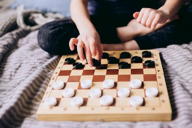Dzieciak wręcza bawić się warcabów stołową grę na łóżku. zostań w domu koncepcja kwarantanny. koncepcja rozrywki gra planszowa i dzieci. czas dla rodziny.