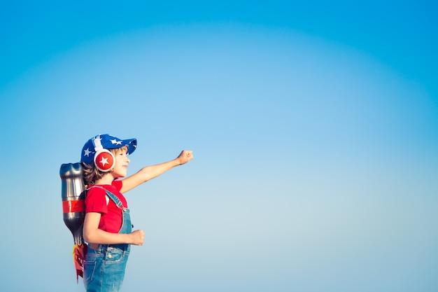 Dzieciak z jet packiem przeciw błękitne niebo. dziecko bawiące się na zewnątrz. koncepcja sukcesu, lidera i zwycięzcy