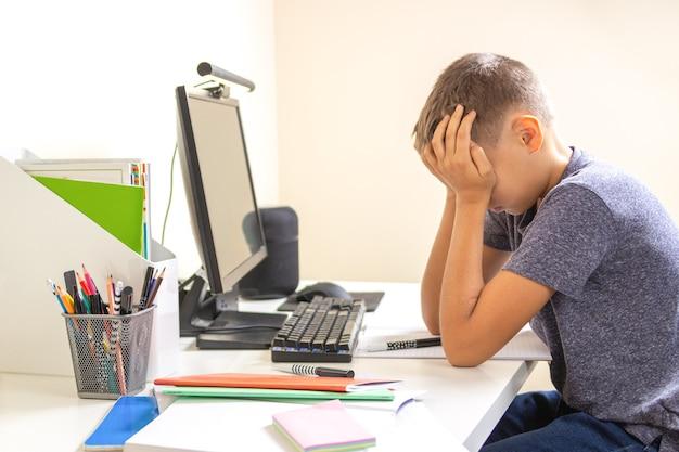 Dzieciak z komputerem odrabiania lekcji w domu.