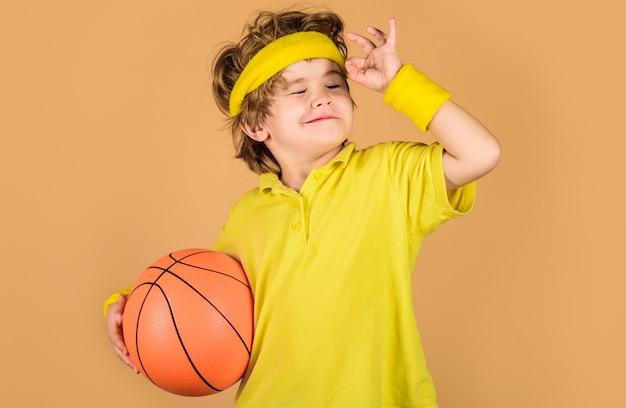 Dzieciak z koszykówką. sportowy chłopiec w odzieży sportowej z piłką. sport dla dzieci. sport aktywny.