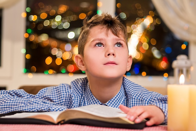 Dzieciak z książką w pobliżu świecy. dziecko dotyka księgi obok okna. życzenie na boże narodzenie. wakacje go inspirują.