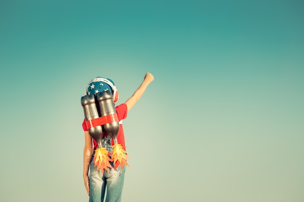 Dzieciak z plecakiem odrzutowym na tle nieba