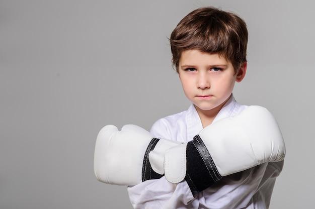 Dzieciak z rękawiczkami bokserskimi pozuje w studiu