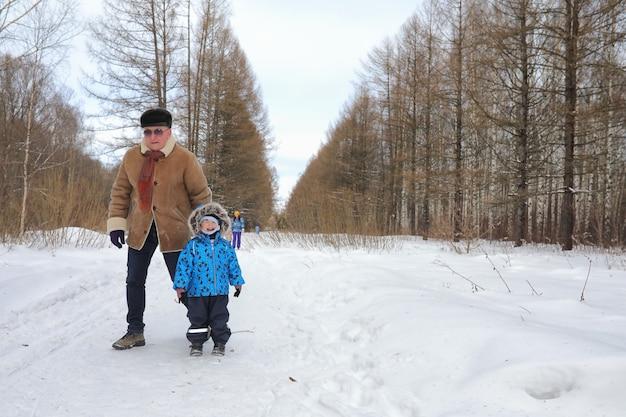 Dzieciak z rodziną bawi się w zimowym parku