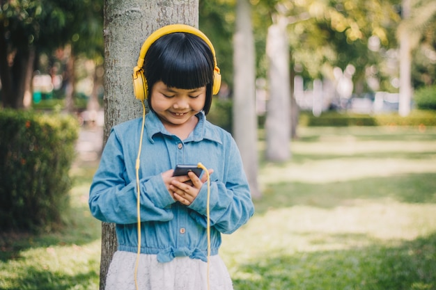 Dzieciaka pojęcie i technologia - uśmiechnięta dziewczyna słucha muzyka z hełmofonami