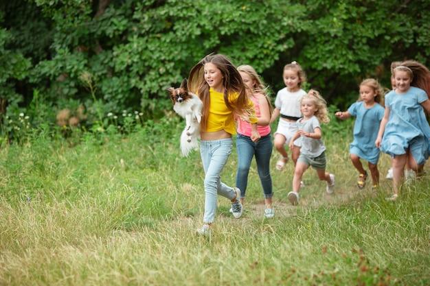 Dzieciaki biegające po zielonej łące