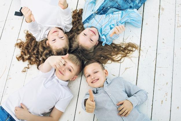 Dzieciaki, chłopcy i dziewczęta, wesołe, szczęśliwe, piękne leżą na białej drewnianej podłodze i uśmiechają się!