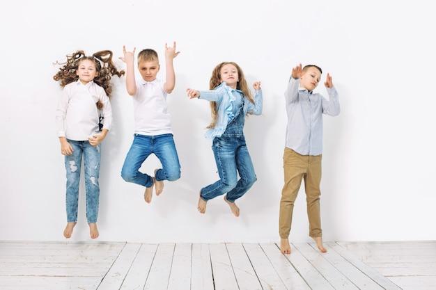 Dzieciaki, chłopcy i dziewczęta, wesołe, szczęśliwe, piękne na tle białej ściany