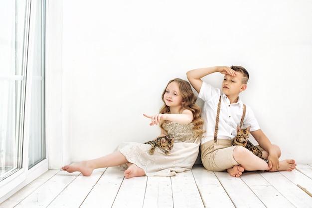 Dzieciaki chłopiec i dziewczynka są piękne i szczęśliwe razem z małymi uroczymi kociętami bengalskimi