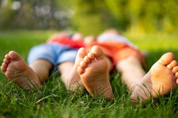 Dzieciaki latem leżą na trawie w parku, zbliżenie nóg dzieci