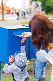 Dzieciaki pomagają matce umieszczać litery w skrzynce pocztowej