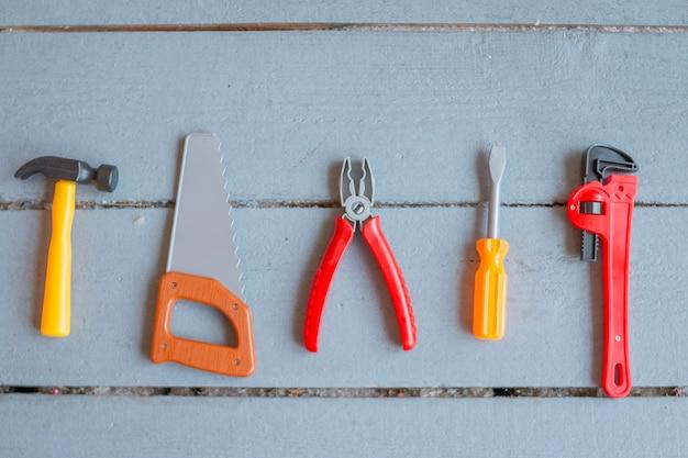 Dzieciaki rozwija zabawki na drewnianym tle. widok z góry. skopiuj miejsce zabawka dla dzieci. narzędzia do zabawy zabawki. mały rzemieślnik