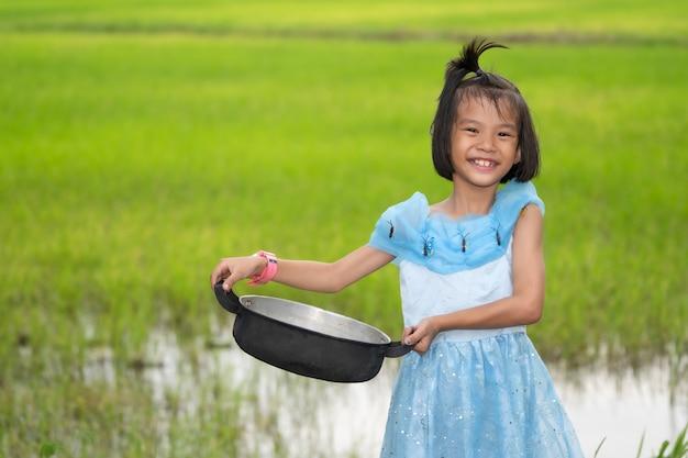 Dzieciaki trzyma karmowego garnek na zamazanym zielonym ryżu polu