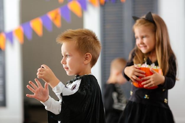 Dzieciaki w karnawałowych kostiumach świętują halloween i bawią się dyniami i cukierkami