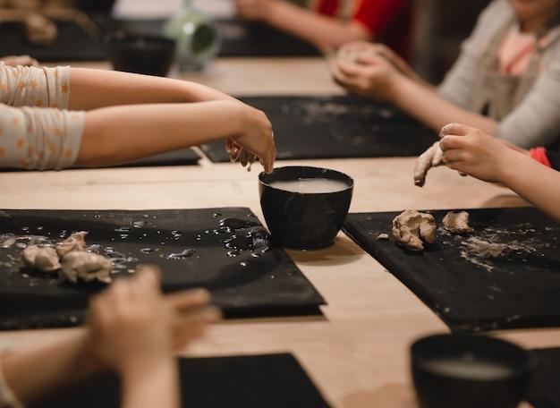 Dzieciaki w warsztacie garncarskim tworzące różne rzeczy z gliny. warsztaty garncarskie.