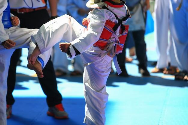 Dzieciaki walczące na scenie podczas turnieju taekwondo