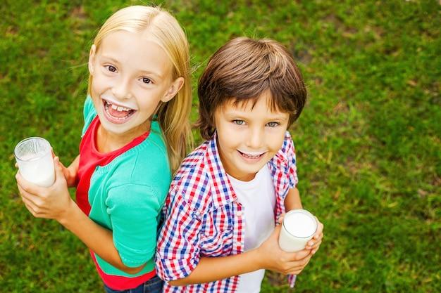 Dzieciaki z mlecznymi wąsami. widok z góry dwóch uroczych małych dzieci z mlecznymi wąsami, trzymających szklanki z mlekiem i uśmiechających się, stojąc razem na zielonej trawie