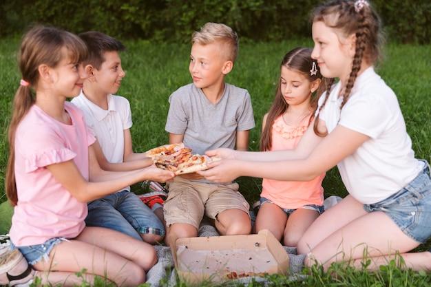 Dzieciaki z przodu dzielą się pizzą