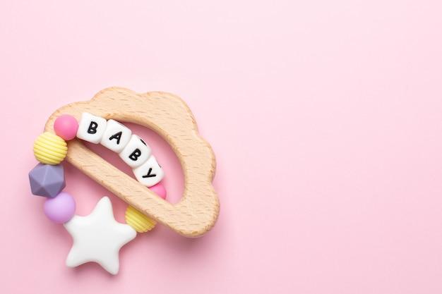 Dziecięca drewniana zabawka i gryzaki w pastelowych kolorach na różowo