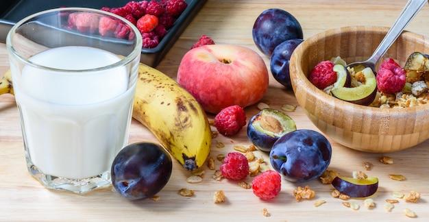 Dziecięca miska śniadaniowa z musli, jagodami, owocami i mlekiem