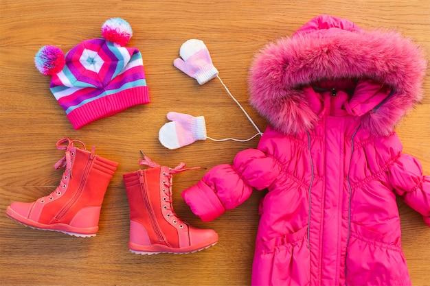 Dziecięca odzież zimowa: ciepła różowa kurtka, czapka, rękawiczki, buty. widok z góry.