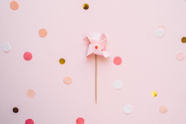 Dziecięca pastelowa nakrywka wiatrowskazów na babeczkę na różowym tle z konfetti. tło uroczysty urodziny