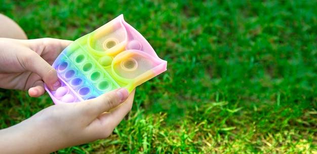 Dziecięca ręka bawi się nowym, modnym antystresowym silikonowym zabawką, pop go na banerze internetowym parku za pomocą
