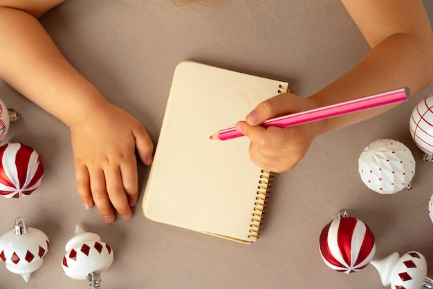 Dziecięca ręka pisząca list do świętego mikołaja na arkuszu notatnika otoczona bombkami