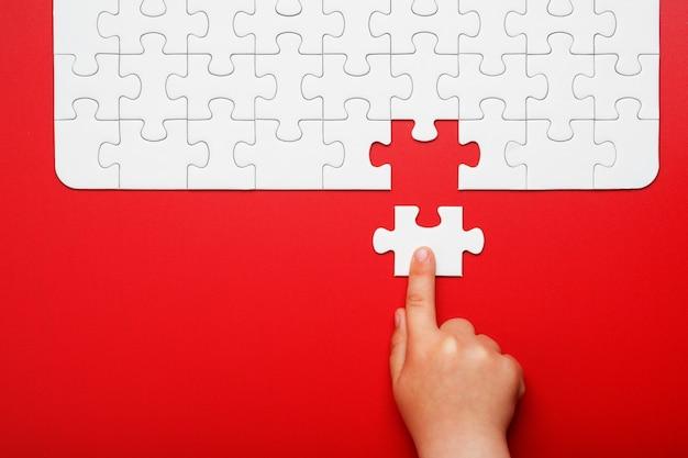 Dziecięca ręka przesuwa kawałek białej układanki na czerwonym tle