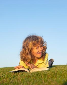 Dziecięca wyobraźnia innowacja i inspiracja dzieci słodkie dziecko czytające książkę na zewnątrz na trawie