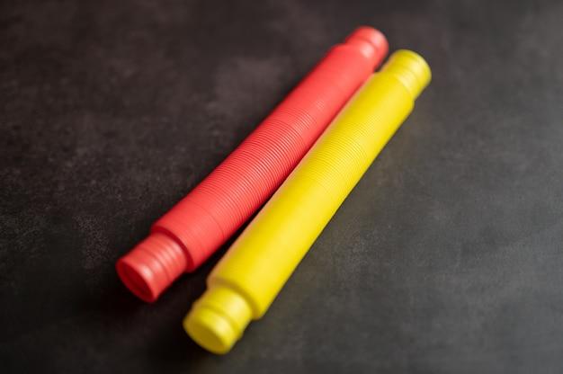Dziecięca zabawka antystresowa sensoryczna pop rurka plastikowa fidget push na czarnym tle stołu lub podłogi. małe zabawki dla dzieci poptube czerwony i żółty odcień jasny kolor, trend 2021 rok. widok z góry, układ płaski