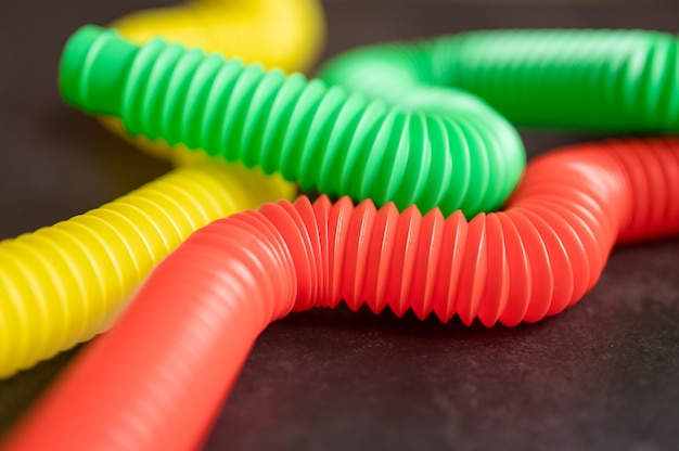 Dziecięca zabawka antystresowa sensoryczna pop rurka plastikowa fidget push na czarnym tle stołu lub podłogi. małe zabawki dla dzieci poptube wielokolorowy odcień jasny kolor, trend 2021 rok