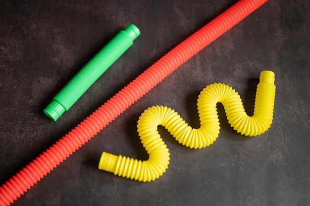 Dziecięca zabawka antystresowa sensoryczna pop rurka plastikowa fidget push na czarnym tle stołu lub podłogi. zabawki dla dzieci małe poptube wielokolorowy odcień jasny kolor, trend 2021 rok. widok z góry, układ płaski