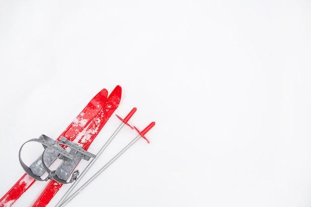 Dziecięce czerwone narty z kijkami - układanie na śniegu. sporty zimowe dla dzieci, zajęcia na świeżym powietrzu, rodzinne zabawy. białe tło naturalne mroźne. skopiuj miejsce.