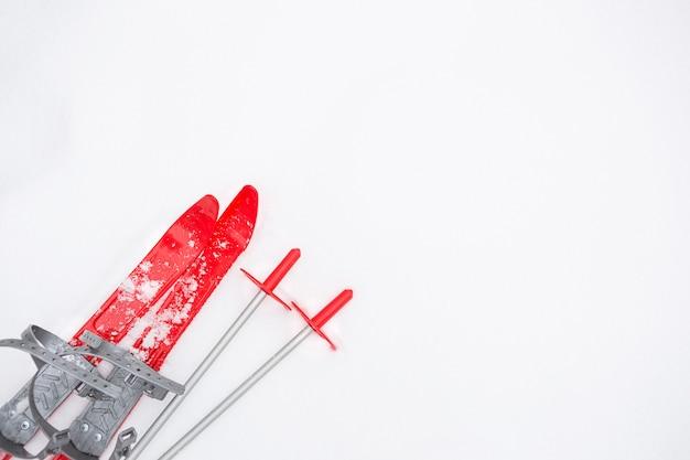 Dziecięce czerwone narty z kijkami - układanie na śniegu. sporty zimowe