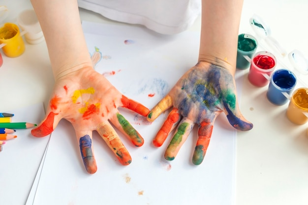 Dziecięce dłonie pomalowane różnokolorowymi farbami