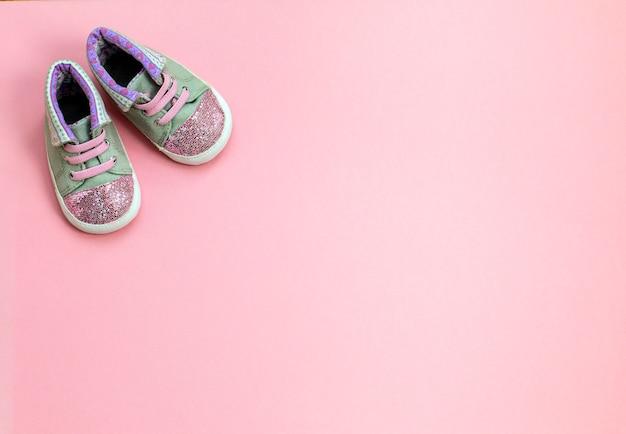 Dziecięce jeansowe buty sportowe dla dziewczynek, stoi na różowym tle.
