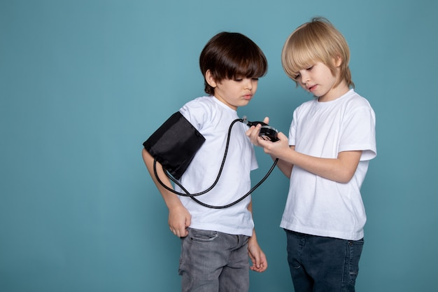 Dziecięce małe słodkie urocze, mierzące ciśnienie w białych koszulkach i dżinsach