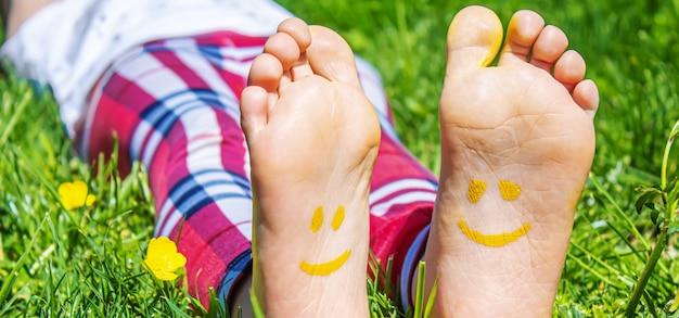 Dziecięce nóżki z wzorem farb uśmiechają się na zielonej trawie. selektywne skupienie. natura.
