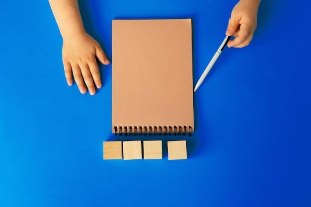 Dziecięce ręce pisania w otwartym notesie, widok z góry, miejsce na kopię