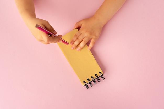 Dziecięce ręce pisania w otwartym notesie, widok z góry