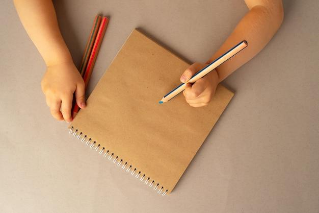 Dziecięce ręce pisania w otwartym notesie
