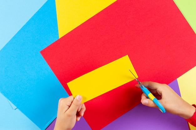 Dziecięce ręce tnące kolorowy papier nożyczkami