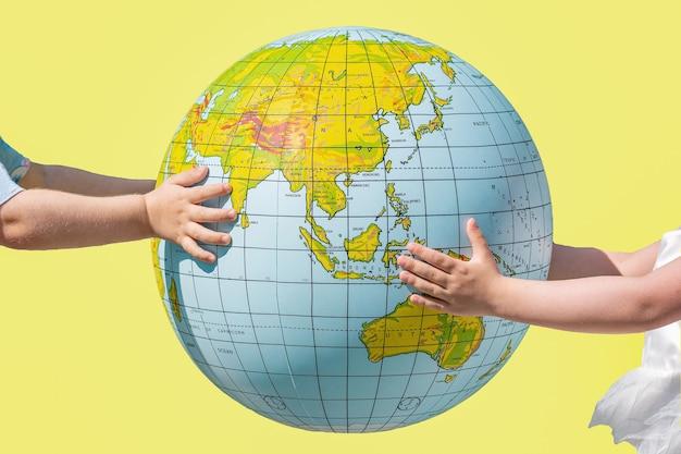 Dziecięce ręce trzymające piłkę w kształcie ziemi, żółte tło.