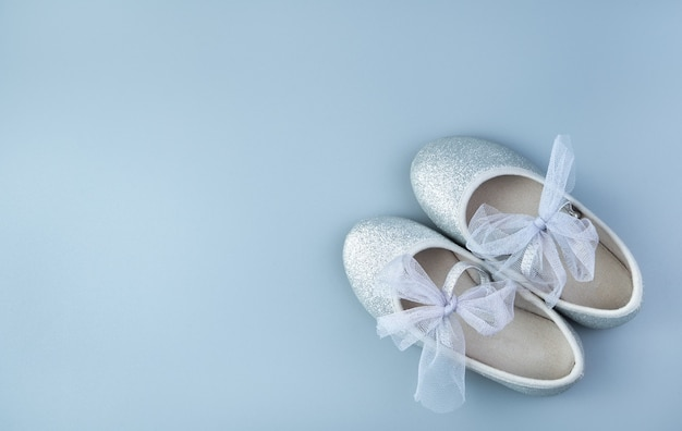 Dziecięce srebrne wakacyjne buty na szaro-niebieskim tle.