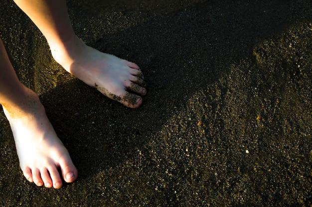Dziecięce stopy na plaży w piasku z bliska